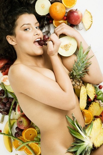 Naked woman lying on fruits and eating grape. : Stock Photo