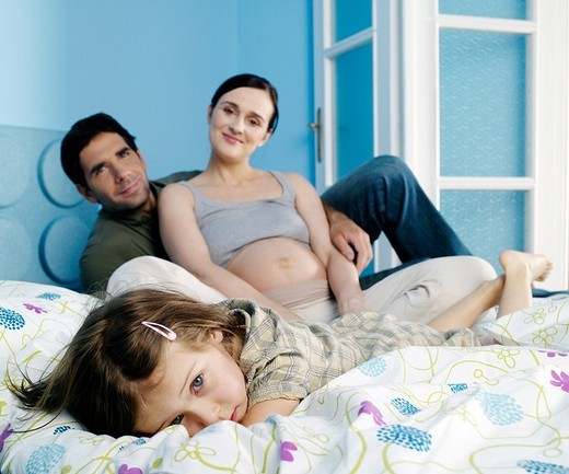 Stock Photo: 4123-8111 Dauther lying in bed with her parents