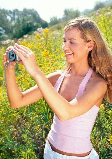 Stock Photo: 4123-8187 Woman with camera on the meadow