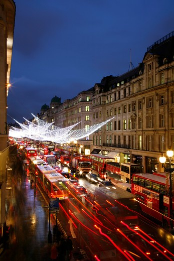 UK, London, Regent Street, Christmas lights and string of London buses : Stock Photo