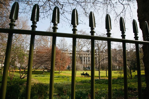 UK, London, Bloomsbury, Gordon Square, View through fence, couple sitting on bench in the background : Stock Photo