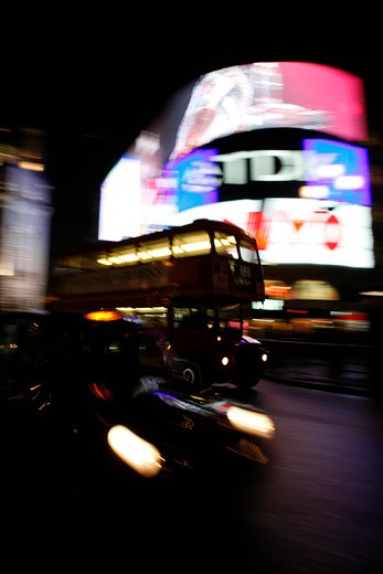 London taxi and bus driving through Piccadilly Circus in London's West End, UK : Stock Photo