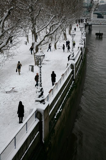 Pedestrians walking by the London Eye on a snowy Queens Walk, South Bank, London, UK : Stock Photo