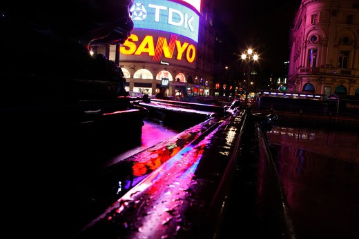 Neon reflections in the Eros fountain, Piccadilly Circus, London, UK : Stock Photo