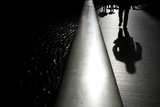 UK, London, Canary Wharf, shadows and silhouettes of pedestrians walking on footbridge across West India Dock South : Stock Photo