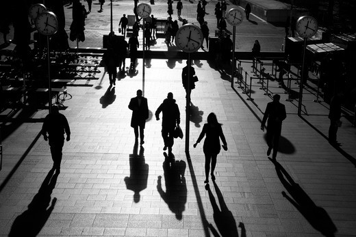 UK, London, Canary Wharf, shadows and silhouettes of pedestrians walking through Reuters Plaza : Stock Photo