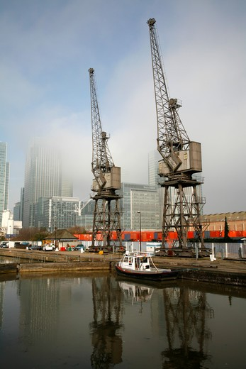 UK, London, Canary Wharf, Cranes on misty West India Dock South : Stock Photo