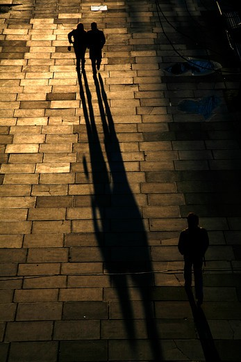 UK, London, Shadows and silhouettes of pedestrians walking along Queen's Walk alongside River Thames at South Bank : Stock Photo