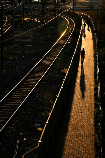 UK, London, Harlesden, Pedestrians walking along footpath leading to Willesden Junction train station : Stock Photo