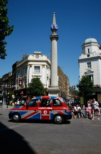 London taxi going round the Seven Dials sundial monument in the middle of Seven Dials, Covent Garden, London, UK : Stock Photo