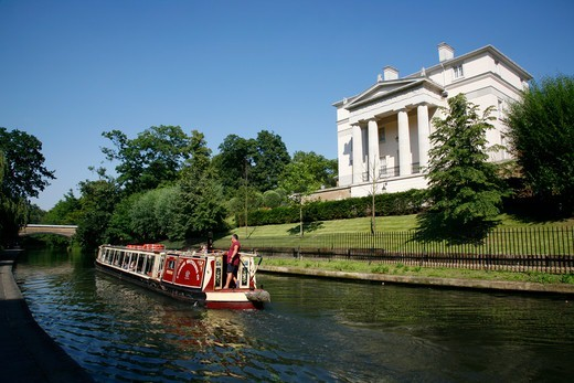 Canal boat on Regent's Canal passing a recent Quinlan Terry-designed neo-Classical villa in Regent's Park, London, UK : Stock Photo
