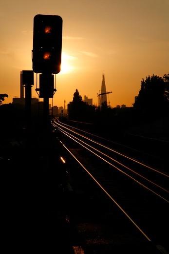 Looking westward at sunset along the railway tracks at Deptford towards the Shard at London Bridge, London, UK : Stock Photo