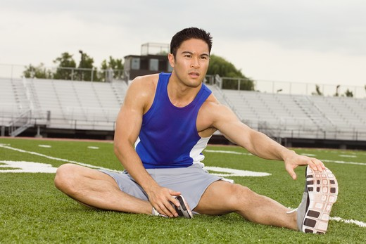 Athlete stretching in a stadium : Stock Photo