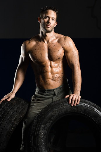 Stock Photo: 4125R-197 Shirtless mechanic with fitness muscles leaning on tires in garage
