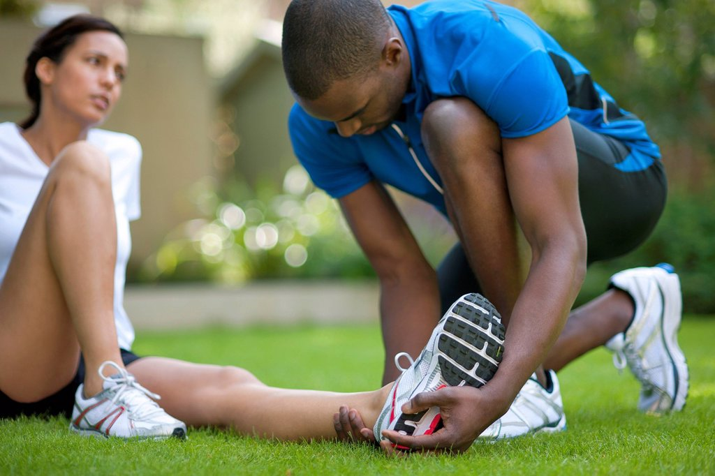 Stock Photo: 4128R-14332 Ankle injury. Female runner with an ankle injury.
