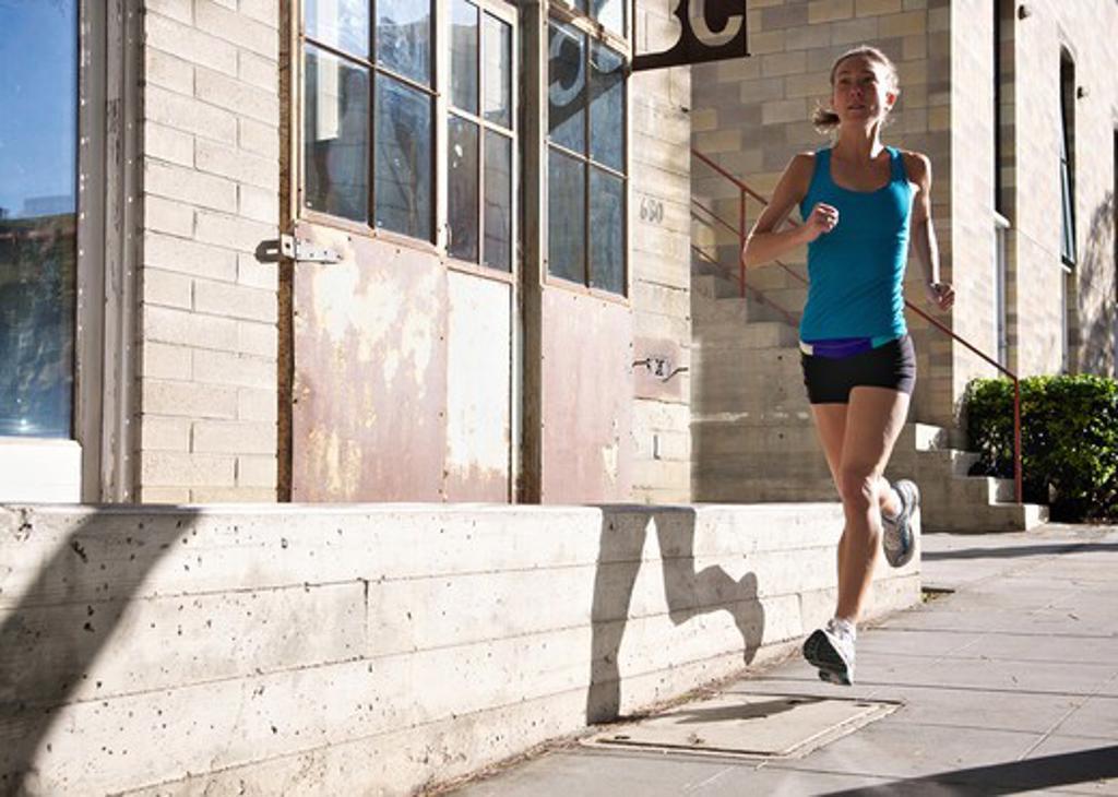 Female athlete running on sidewalk, Midtown, San Diego, California, USA : Stock Photo
