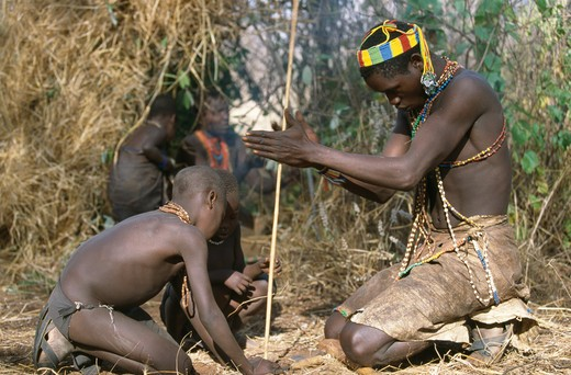 hadzabe man teaching children how to start a fire with a stick lake eyasi area, tanzania : Stock Photo