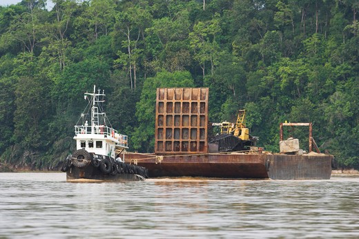 heavy machinery being moved by boat in the timber/oil palm industry. kinabatangan river sabah borneo. : Stock Photo
