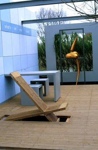 Stock Photo: 4141-37213 chair in decking with walls & contemporary sculpture. photographed at floriade, holland (netherlands). contemporary garden designed by buro landvast - 'whats on your mind'.