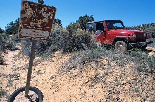 Stock Photo: 4141-41278 bullet riddled sign stating that the area is closed to all vehicle use. a jeep is parked nearby. off road rage?