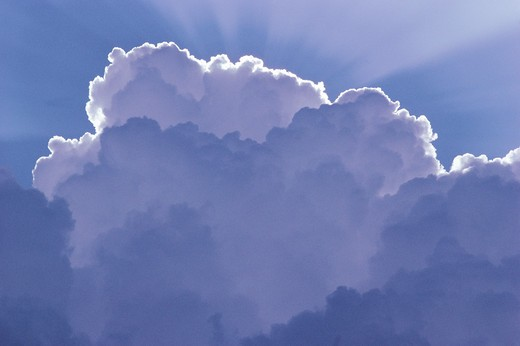 shower cumulus cloud with rays emanating from sun behind cloud : Stock Photo