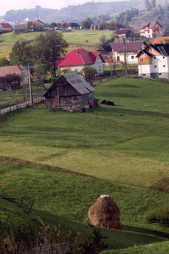 Hayrick In Traditional Meadows Southern Carpathian Mountains With Alpine Village, Saxon Part Of Transylvania, Romania. : Stock Photo