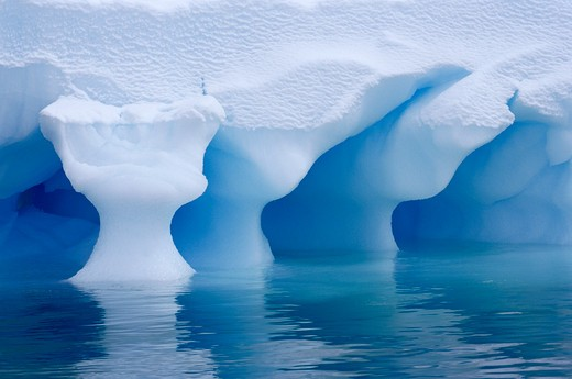 sculpted iceberg shape produced by wave action antarctica : Stock Photo
