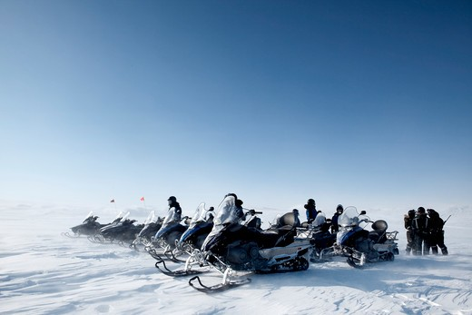 A group of snowmobiles travelling accross a barren winter landscape : Stock Photo