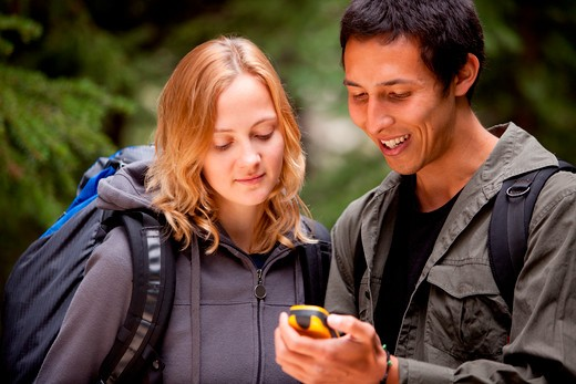 Two friends geocaching in the forest wth a gps : Stock Photo