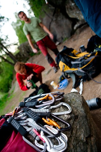 Stock Photo: 4148R-2552 A pile of quick draw carabiners with climbers out of focus in the background.