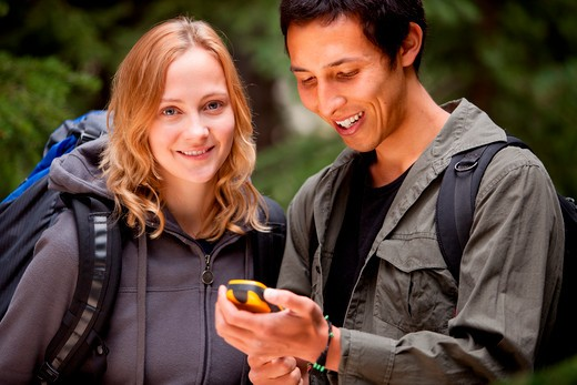 A man and woman looking at a gps in the forest : Stock Photo