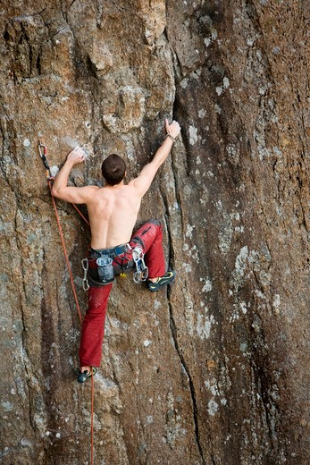 A male climber against a large rock face climbing lead against a magnificant landscape. : Stock Photo