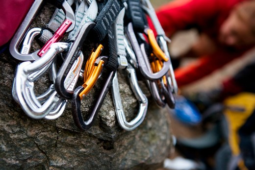 A pile of quick draw carabiners with climbers out of focus in the background. : Stock Photo