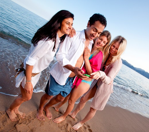 A group of friends laughing at a cellphone, funny text message or picture : Stock Photo