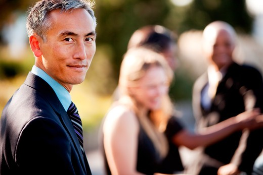 Stock Photo: 4148R-2577 A group of business people outside - sharp focus on Asian man in foreground