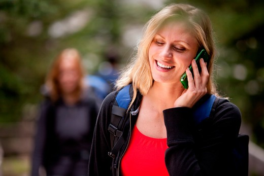 Stock Photo: 4148R-2609 A happy woman talking on a cell phone outdoors