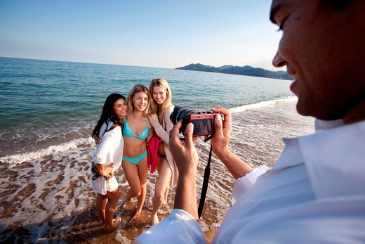 Stock Photo: 4148R-2617 A man taking a photo of three women at the ocean.