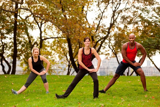 Stock Photo: 4148R-2640 A group of people stretching in a park - focus on front woman