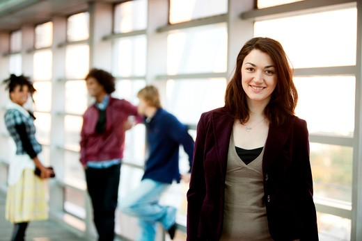 Stock Photo: 4148R-2648 A portrait of a young woman with friends in the background