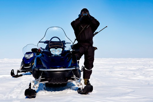 An expedition guide and a couple of snowmobiles on a winter landscape : Stock Photo