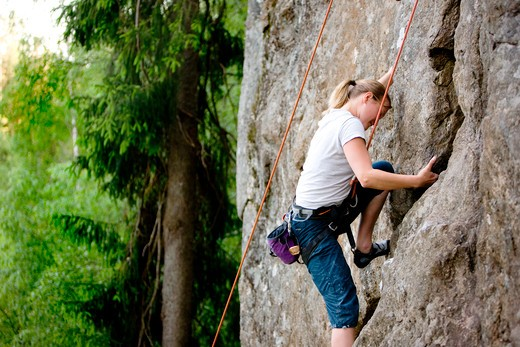 Stock Photo: 4148R-2664 A female climber, climbing using a top rope on a steep rock face (crag)