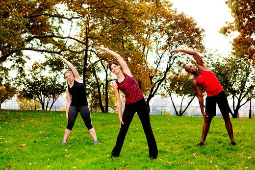 A group of people stretching in a park : Stock Photo