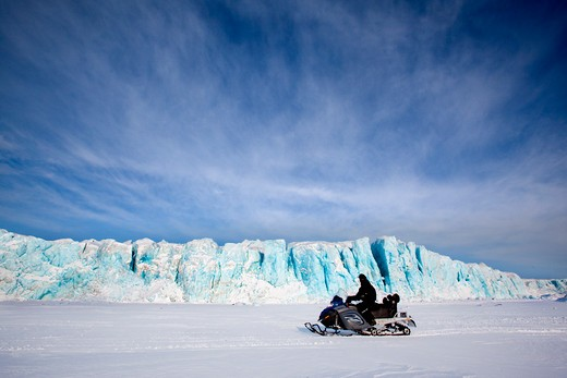 A glacier in Svalbard, Norway with a skidoo travelling on the ice : Stock Photo