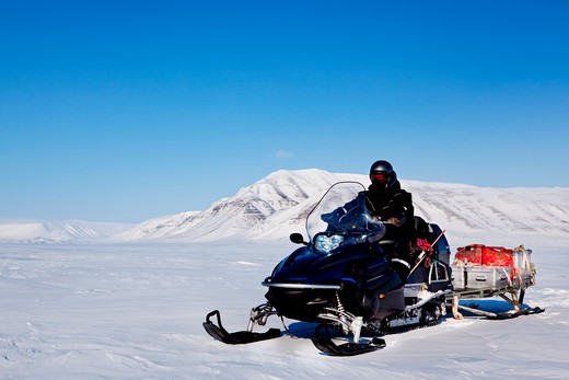 A snowmobile on an arctic expedition on a frozen lake : Stock Photo