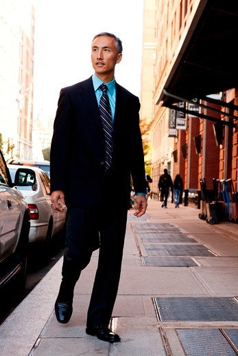 A business man in a city setting on a sidewalk : Stock Photo