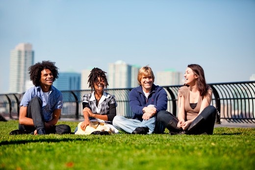 A group of friends in a city park talking and laughing : Stock Photo