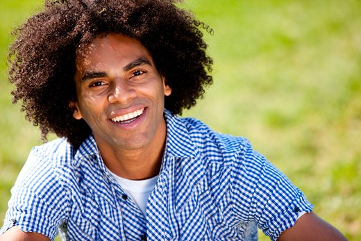 Young man smiling at camera in a park. Horizontally framed shot. : Stock Photo