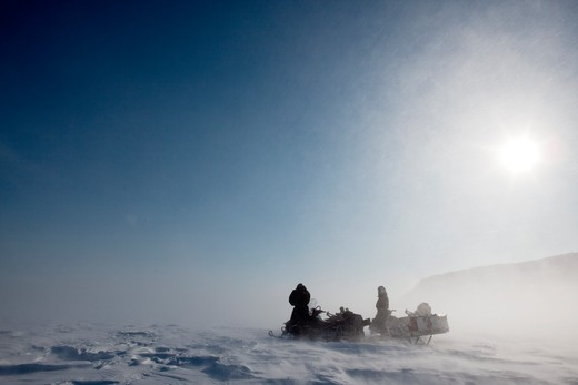 A pair of snowmobiles in a winter blizzard with blowing snow : Stock Photo