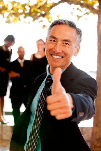 An asian looking business man with thumbs up - critical focus on eyes : Stock Photo