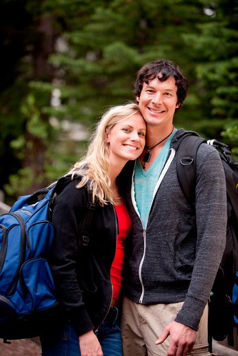 A young man and woman outdoors in the forest : Stock Photo